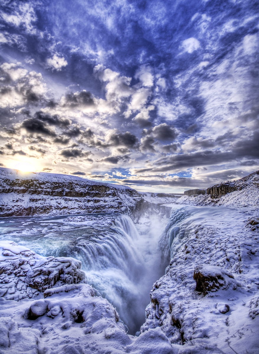 The Icy Pit to Hell This is Gulfoss, the frozen waterfall in Iceland. Dark age theologians used to believe this was the entrance to hell, which was originally a cold place; the innermost circle of Dante's version was frozen. True believers would come here and cast themselves down into the chasm to try to rescue souls they were told had gone to hell.It's hard to describe how slippery this place is. I guess I could say it's slippery as hell. The ground is already solid ice, and then there is a fine mist from the waterfall that forms tiny little perfect spheres on top that somehow take friction into a negative physics impossibility.- Trey RatcliffClick here to read the rest of this post at the Stuck in Customs blog.