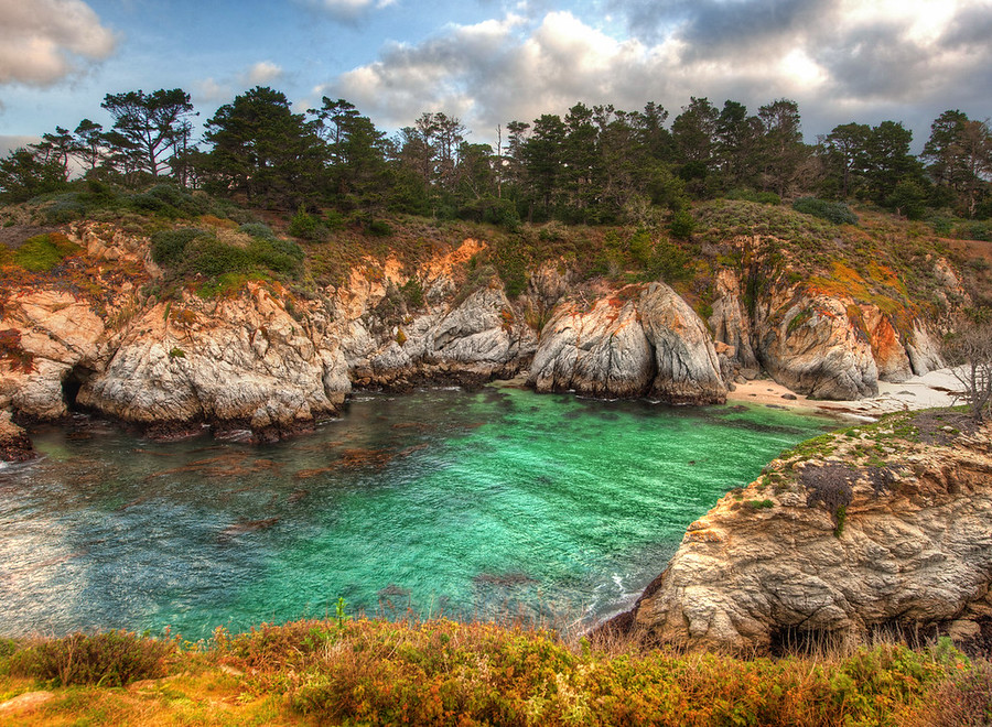 Hiking in CarmelJust south of Carmel-by-the-Sea is a hiking trail that goes along the coast.  I went down at sunrise one morning to see what I could find.  The entrance to the trail was blocked by a gate, and there was no ranger in the little box-place where rangers stand.  I was bamboozled.  There was no way through or around.  I could have walked, but it looked like the road went on quite a ways before the parking lot.So I waited until some other guy came along to let himself in.  I was parked a ways back, and so I got his attention from afar by grunting and raising my Nikon-on-tripod over my head like a sand raider -- he got the message and waved me through.- Trey RatcliffRead the entire post at the Stuck in Customs blog.