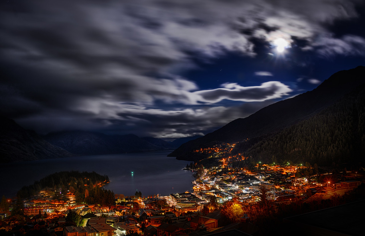"Moonlight Clouds – Queenstown at 7:30 AMThe winter in these southern places make the sunrise rather late! I took this about 7:30 AM in the morning while the moon was still out over the sparkling Queenstown. I set up the tripod on my balcony, and this is our amazing view! I'm renting a Bach here called ""The Nest"" – and it has incredible views all day long… and all night long too, as you can see! :)- Trey RatcliffClick here to read the entire post at the Stuck in Customs blog."