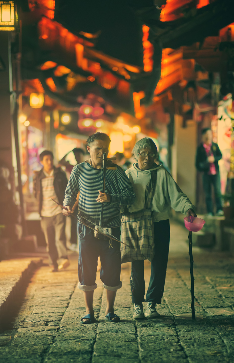 Walking Blind through China As Tom Anderson and I were leaving the old area of Lijiang one evening, we saw these two coming towards us in the opposite direction. One of them was blind (perhaps both), and one played a small stringed instrument while the other held out a bowl for donations.I squatted down and waited for them to enter a little pool of light from a nearby shot before I took the photo. And then I walked over and put a little donation in the bowl.- Trey RatcliffClick here to read the rest of this post at the Stuck in Customs blog.