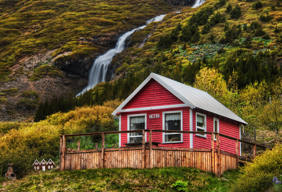 "Little Elves, Little WaterfallGoing into one of the valleys by Isafjordur takes you to many little homes near waterfalls.  I thought this one was quite lovely.And if you look to the left there, you'll see the tiny homes they also built for the elves.I was editing this photo at dinner one evening in Isafjordur.  One of the waitresses saw this house, recognized it, and said, ""Oh that's jklasdj(jkasdj^dhsaj"".  Of course, I am doing my best to approximate the Icelandic language there...- Trey RatcliffRead the rest here at the Stuck in Customs blog."