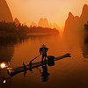 "<h2>The Morning Fisherman</h2> <br/>Now, getting to this place was not easy!<br/><br/>I arrived about 1 AM at a tiny family-run inn by the river.  I was meeting a local guide at 5 AM, so I didn't get a lot of what I would call ""quality sleep"".  Anyway, I got up very early and went downstairs in pitch black.  There seemed to be a big white cloth box I had to go around to find the front door.  My guide was outside.  The door was locked and we could not figure out how to get it open.  Everyone at the little inn was sound asleep and I was totally confused.  Then, from inside the big white box, a body flew out of it!  There was a 60-year-old Chinese guy inside that was sleeping until I woke him up with all my lock-manipulations.  His naked limbs in the white sheets scared the bejeezus out of me and woke me right up!<br/><br/>And then we were on the river about 5:15.  It was still completely dark outside.  And I mean COMPLETELY DARK.  It was a thin bamboo raft with an outboard motor.<br/><br/>I turned around to ask my guide, ""How the heck does the boat driver know where he is going?!?""<br/><br/>He calmly said, ""Oh, no worry.  The river is very wide.""<br/><br/>I not-calmly said, ""Well, that's great and everything, but I can't even see the edge to the river!""<br/><br/>He calmly said, ""But it is so wide.""<br/><br/>This line of questioning was not getting me anywhere, so I just decided to sit back and enjoy my possible last moments on Earth.  Then the sun started to rise, and we moved the boat over to the best bank for the angle.<br/><br/>Want to hear something amazing about these fishermen?  You won't believe it... but maybe others can confirm this! The fishermen use these two trained cormorant birds that have their throats tied.  The birds dive into the water, eat a fish, but then can't swallow it because of the rope.  The fisherman rudely pulls the fish from the bird's throat and drops it into that basket behind him.  The bird then goes over to a tiny keyboard and sends out the tweet, ""WTF"".<br/><br/>- Trey Ratcliff<br/><br/><a href=""http://www.stuckincustoms.com/2010/10/16/the-li-river/"" rel=""nofollow"">Click here to read the rest of this post at the Stuck in Customs blog.</a>"