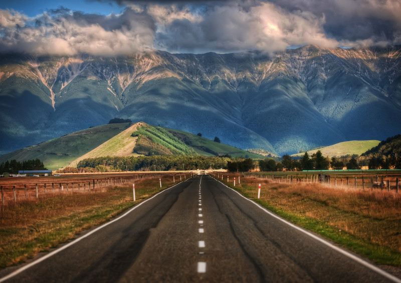 "<h2>The Long Road to New Zealand</h2> <br/>This is one of countless beautiful roads that crisscross New Zealand.  I'm afraid I've forgotten exactly where I was when I took this photo!   I know that is very lame, but I bet people around here can help me pinpoint the area.<br/><br/>As far as the camera settings, this is the kind of shot you can get with something called ""compression,"" a method where you use a zoom lens and zoom in quite far.  It takes images in the distance and makes them larger than life.<br/><br/>- Trey Ratcliff<br/><br/>Read more <a href=""http://www.stuckincustoms.com/2011/12/31/the-long-road-to-new-zealand/"">here</a> at the Stuck in Customs blog."