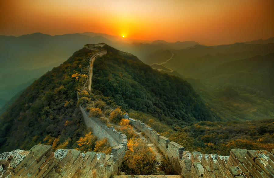 -The Great Wall of China-Wow I was alone here. As I walked along this ancient, original stretch of the Great Wall, I felt the ghosts haunting the old towers and little enclaves.I finally found an extremely remote part that is far enough away from civilization to stay pure. The ruins of the wall in this area has been overgrown with vegetation. When you walk along the top, you have to snake your way between huge bushes and all sorts of trees. Stairs and parts of the walkways have crumbled away in the past thousand years. The old towers are slowly fragmenting as lichens and moss cover parts of the stone that are decaying away.This has only reminded me that the main tourist part of the Great Wall is a very tiny stretch that has been re-built in recent years… so it is all fake and kind of Disney-wall. I don't think I like that…That day I walked from tower to tower, looking at the sinuous wall as it snakes over the mountains. It's so huge that I won't even begin to come up with analogies… but, speaking of snakes, a family here told me to watch out for them. I kept that in mind as I hiked back in the pure black of night. I had a little flashlight to keep me company, along with my music. I didn't see any snakes, and I didn't fall down, so all together it was a great day and night.