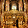 "<h2>Ghost in the Cathedral</h2> <br/>The Byzantine gold glowed hot when I got inside, a divine signal to me that God was mad because I brought my camera inside.  However, I reasoned with God, the sign read ""No Cameras"" in a Cyrillic lettering, a lettering style I do not recognize since the Jesuits trained me in the Romance languages and not these Slavic uncials.<br/><br/>Besides, I was inside Saint Michael's Cathedral, and I was holding a camera, and, as the saying goes, when in Rome, <a href=""http://www.flickr.com/photos/stuckincustoms/sets/72157594201844069/"">shoot interiors of churches in Rome</a>, and when in Kiev, break Eastern Orthodox Ecumenical Councils.<br/><br/>While God was busy figuring out my flawless reasoning, I spotted a cloaked HeiroMonk in is post-Matins chanting, moving in a pattern indecipherable by my camera, thus the ghostly visage in this seeming partial transcendence.<br/><br/>- Trey Ratcliff<br/><br/><a href=""http://www.stuckincustoms.com/2007/02/01/ghost-in-the-cathedral/"" rel=""nofollow"">Click here to read the rest of this post at the Stuck in Customs blog.</a>"