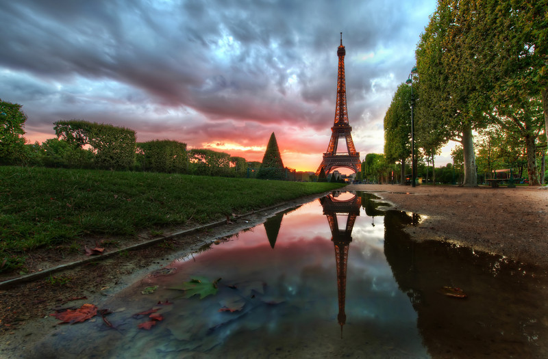 "<h2>Reflections on the Eiffel Tower</h2> <br/>Isn't it romantic?  What could be more perfect than a beautiful sunset here in Paris?<br/><br/>There was a big storm all day long, but I could see the clouds were beginning to break up a little to the west, and I knew there was a possibility the sun would dip into an opening beneath the heavy clouds.  So, with that intense possibility, I headed over to the Eiffel Tower area hoping the light would turn out right...<br/><br/>I also made a behind-the-scenes video.  Since you guys have been so nice over on Google+, I'll share that video exclusively there first, so be sure to stay tuned... I'm still editing the thing together!<br/><br/>- Trey Ratcliff<br/><br/>Read more <a href=""http://www.stuckincustoms.com/2011/07/22/paris-effel-tower/"">here</a> at the Stuck in Customs blog."
