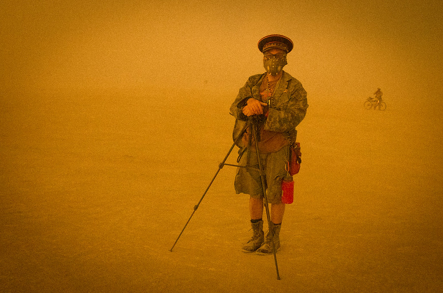 On one of the final afternoons, a bitter sandstorm blew across the playa. It was also the night of the big burn, so people began to amass near the man himself. I saw this fellow photographer setting up on the periphery, bracing himself against the storm.