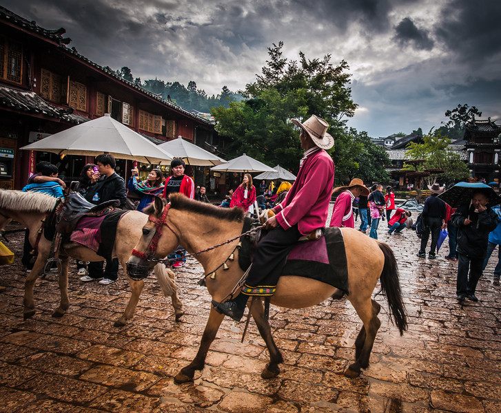 "<h2>Man on Horse in Lijiang Square</h2> <br/>When I arrived into the middle of this opening within the tight city of Lijiang, a fresh rain had just made everything nice and slick. There were a few men walking around the old town square on horses in the midst of all the pedestrian activity. <br/><br/>- Trey Ratcliff<br/><br/><a href=""http://www.stuckincustoms.com/2012/10/24/man-on-horse-in-lijiang-square/"" rel=""nofollow"">Click here to read the entire post at the Stuck in Customs blog.</a>"
