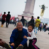"<h2>Boy and Grandfather at Tiananmen Square</h2> I was walking through Tiananmen on a white-out cloud day taking photos of people. I had on my earphones and was kind of drifting in and among the crowd. It's a bit like being in a movie when you do this... anyway, I'm sure you've heard me mention it before, so I won't go into details.  It's often a very nice way to make things timeless... to separate people and objects from their place and time.  These two were on the ground wrestling and having fun.  I squatted about 15 feet away to take a photo, and they were most delighted!  - Trey Ratcliff  From the <a href=""http://www.stuckincustoms.com/2011/09/12/boy-and-grandfather-at-tiananmen-square/"">blog post</a> at www.stuckincustoms.com."