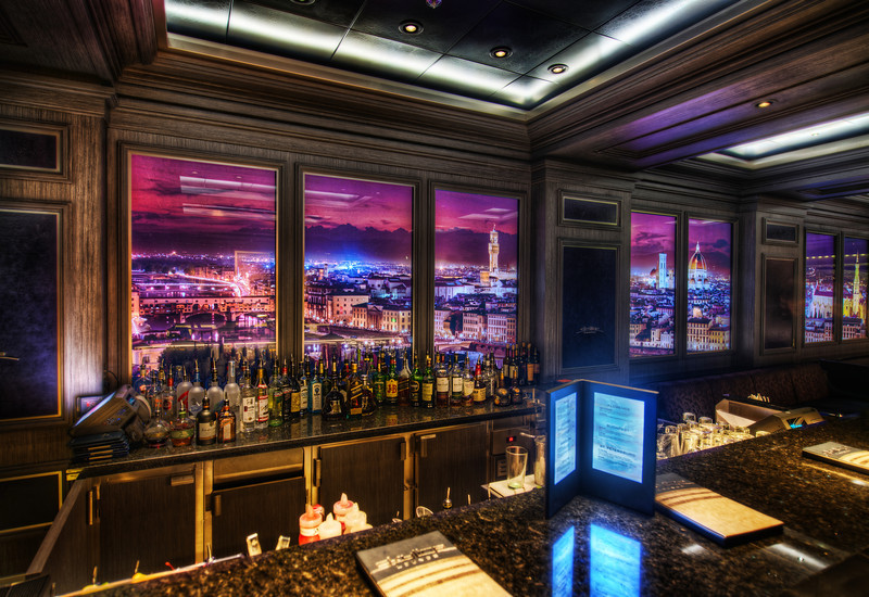 "<h2>Disney Fantasy Cruise - The Skyline Bar</h2> Which city do you think this is??<br/><br/>This is the coolest bar on the ship.  I was in here this night with John Lasseter (I think!) - but he was sitting with a group of people and I didn't want to interrupt him to say hello.  Anyway, these walls are filled with images of different cities that change out every 12-14 minutes or so.  And, if you get up close to these hi-def walls, you can see movement!  People walk around the streets, cars move, lights flicker, people go about their days inside their homes, etc.  It's endlessly fascinating.  I also have some video of this too -- I'll release that as soon as I have more bandwidth at dock!<br/><br/>- Trey Ratcliff<br/><br/><a href=""http://www.stuckincustoms.com/2012/04/06/disney-fantasy-cruise-the-skyline-bar/"" rel=""nofollow"">Read the rest of this post at the Stuck in Customs blog.</a>"