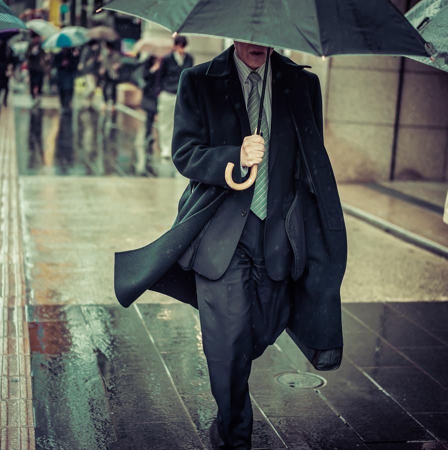 man with umbrella in tokyo rain stuck in customs
