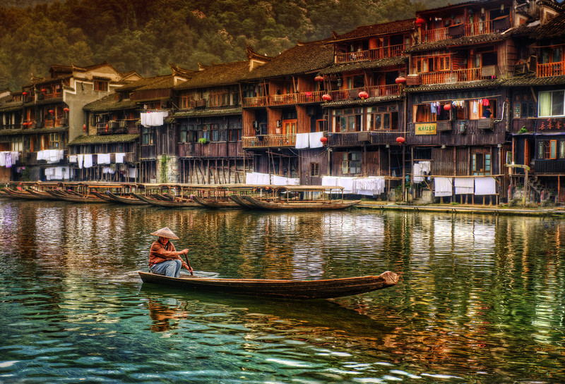 """<h2>Boat in Feng Huang</h2> It was a cool and calm afternoon in the ancient and impossible town of Feng Huang. It's an old town, wreathed in many legends.  On the old river, you can occasionally see a boat passing here and there. The boatmen come in all shapes and sizes, but many wear the same hat and style. It is absolutely like a warp of time...  - Trey Ratcliff  Read more <a rel=""""nofollow"""" href=""""http://www.stuckincustoms.com/2012/02/11/boat-in-feng-huang/"""">here</a> at the Stuck in Customs blog."""