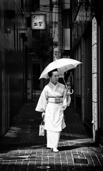 """<h2>Umbrella in the Sun</h2> <br/>Tokyo has so many neighborhoods! There are dozens and dozens, each one like it's own mini-city with its own culture and memes. This one (I'm afraid I've forgotten the name) is filled with an older, traditional feel. It's not uncommon to see women come out and walk the street in traditional dress.<br/><br/>- Trey Ratcliff<br/><br/><a href=""""http://www.stuckincustoms.com/2013/06/30/umbrella-in-the-sun/"""" rel=""""nofollow"""">Click here to read the rest of this post at the Stuck in Customs blog.</a>"""