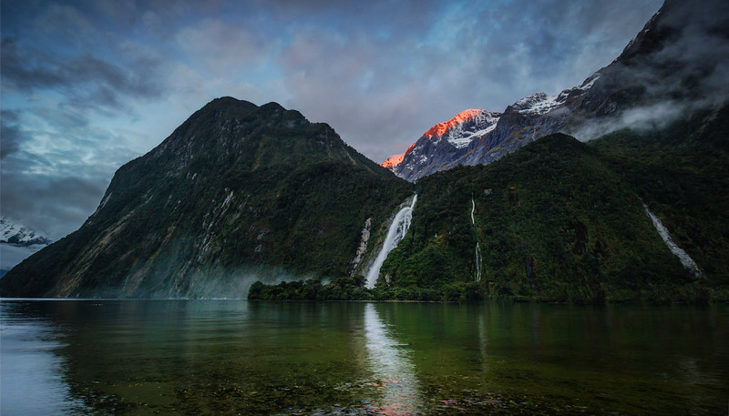 """<h2>Bowen Falls in Milford Sound</h2> <br/>This is one of many sights we'll be seeing together if you come down here to New Zealand. This place is quite the turkey shoot! There's beautiful bits all around.<br/><br/>The best way to get to this particular spot is to get off the walking path and work your way across the rocks. I prefer the view where you are looking across the water… The conditions change quite violently depending on the light and the amount of rain. Sometimes, after a fresh rain, that waterfall is absolutely insane! In this photo, it's still pretty crazy, but only of average sanity.<br/><br/>- Trey Ratcliff<br/><br/><a href=""""http://www.stuckincustoms.com/2012/11/21/new-zealand-events-get-ready/"""" rel=""""nofollow"""">Click here to read the rest of this post at the Stuck in Customs blog.</a>"""