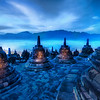 "<h2>The Beating Hearts of the Buddhas</h2> <br/>The morning fog coming off the top of the jungle trees was not like anything I had seen before.  There was just enough morning light to give everything a twilight blue and paint the mountains in the distance a deeper color.<br/><br/>I tried something a little bit different with this photo.  I was holding two flashlights to help me climb the temple in the morning. I think I got there about 5:30 AM when it was still pitch black, so the flashlights helped me find the right footholds and whatnot.  Anyway, this was an extremely long exposure, so I used some of that time to ""paint"" the inside of the bell cages with the beams of my flashlights.  Each of those bell cages held a solitary outward-facing Buddha.  I'm glad I was there alone, because I'm sure I looked like a loon running around shining the flashlights in patterns to illuminate the Buddhas inside.<br/><br/>- Trey Ratcliff<br/><br/><a href=""http://www.stuckincustoms.com/2009/06/23/the-beating-hearts-of-the-buddhas/"" rel=""nofollow"">Click here to read the rest of this post at the Stuck in Customs blog.</a>"
