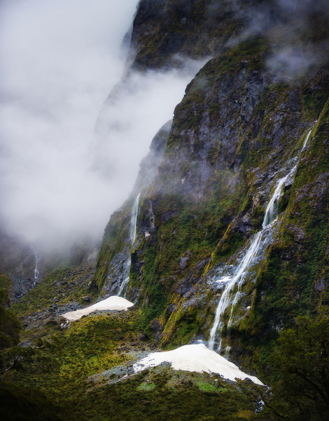 """<h2>Waterfalls on the way to Milford Sound</h2> <br/>There is a good question that will never be answered: Is the drive to Milford Sound equal to the epicness of Milford Sound itself? No one knows!! I can't figure it out. But, one random element that comes into the equation is the rain. When it is raining (or a recent rain), there are over 100 waterfalls that decorate the steep valley.<br/><br/>It's kind of hard to shoot waterfalls in the rain. Actually, it's really hard. I usually amp up my ISO and drop my F-stop very low to make sure I get a quick picture before the rain settles on my lens.<br/><br/>- Trey Ratcliff<br/><br/><a href=""""http://www.stuckincustoms.com/2013/04/04/waterfalls-on-the-way-to-milford-sound/"""" rel=""""nofollow"""">Click here to read the rest of this post at the Stuck in Customs blog.</a>"""