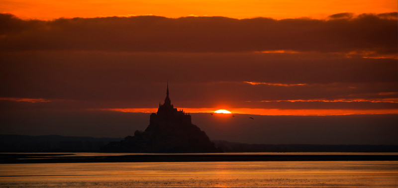 """<h2>Mont Saint Michel at Sunset</h2> </br>Oh my god getting to this location at the last second was difficult and lucky.<br/><br/>I started the wild car ride about 30 minutes beforehand inside that walled city. I looked on Google Maps to figure out how to get to this exact spot. Now, I had no mobile internet, so I basically had to memorize the way here. It required going through, and I kid you not, about seven different roundabouts, each one exiting in a strange, non obviously spot. Anyway, to my and Tom's surprise, I exited each one perfectly and made it here with ZERO mistakes. Note that I am not nearly always this flawless, but it worked out and we got here just in time for sunset!<br/><br/>- Trey Ratcliff<br/><br/><a href=""""http://www.stuckincustoms.com/2013/04/15/mont-saint-michel-at-sunset/"""" rel=""""nofollow"""">Click here to read the rest of this post at the Stuck in Customs blog.</a>"""