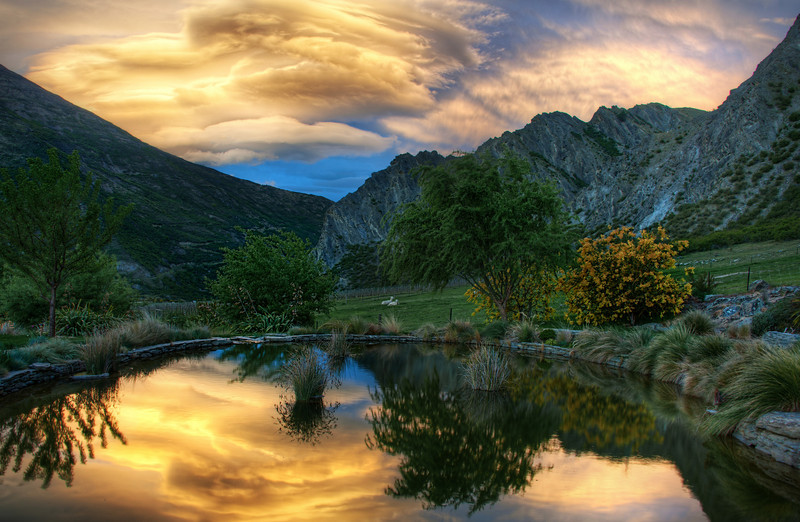 """<h2>The Pond and the Sunset Stormclouds</h2> <br/>I had a wonderful evening with Eden Brackstone, even though he uses a Canon.  I can overlook these trifle matters, but I do not forget them lightly.<br/><br/>We were in Gibbston, New Zealand, about 20 minutes from Queenstown.  After a wonderful dinner with his delightful family, I popped out onto his farm to shoot some HDR.  He started recording video on his aforementioned Canon-thing, and put together the little dealio at the link below.  Enjoy!<br/><br/>Here is the final photo that was taken just before I we started recording the video.<br/><br/>- Trey Ratcliff<br/><br/>See the video <a href=""""http://www.stuckincustoms.com/2010/11/10/new-video-on-edens-farm/"""">here</a> at Trey Ratcliff's travel photography blog, Stuck in Customs."""