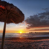 "<h2>Under the Umbrella at Sunset</h2> <br/>We took this during our fun PhotoWalk in San Clemente. It's a wonderful beach there - not too crowded, a perfect beach, and an idyllic pier.  Just throw in a few clouds, and we end up with a perfect sunset!<br/><br/>Every 100 feet or so, these thatched-roof umbrellas are spread out.  Composing with these and a wide-angle lens is kind of challenging, but fun.  I noticed that after I got a wide-angle lens that it opened up a whole new range of compositional complexities. Walking around a scene has to be done with a whole new perspective, since you are able to capture more than a human can see in a single viewing-cone.  But, the challenge is kind of fun to compensate for the lens and try to put together something that feels right.<br/><br/> - Trey Ratcliff <br/><br/>The rest of this entry can be found <a href=""http://www.stuckincustoms.com/2010/10/24/under-the-umbrella-at-sunset"">here</a> at the Stuck in Customs blog."