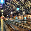 "<h2>Milan Train Station at Midnight</h2> <br/>If you want to see how I made this (and how you can too!), visit my HDR Tutorial. I hope it gives you some new tricks!<br/><br/>I had a super-long day in Milan. I was tired and just wanted to go back to the hotel to have a cappuccino in the bar and edit photography on my laptop. But I remembered the really pretty train station and how I wanted to get a shot with nobody around.<br/><br/>I went in around midnight, found the perfect spot, and then shot away.<br/><br/>The HDR process always takes that slick concrete and makes it extra-reflective. Reflective ground is always great for photography. Also, people always think that I ""colored"" the lights up at the top, but I did not. In fact, I never ""paint"" on my photos. Any color that you see in them was actually there, except in the cases when I apply a texture treatment.<br/><br/>- Trey Ratcliff<br/><br/><a href=""http://www.stuckincustoms.com/2006/08/10/milan-train-station/"" rel=""nofollow"">Click here to read the rest of this post at the Stuck in Customs blog.</a>"
