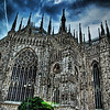 "<h2>Dark Duomo</h2> <br/>Mark Twain said the following of the Duomo in Milan in his work, Innocents Abroad:<br/><br/>What a wonder it is! So grand, so solemn, so vast! And yet so delicate, so airy, so graceful! A very world of solid weight, and yet it seems ...a delusion of frostwork that might vanish with a breath!...The central one of its five great doors is bordered with a bas-relief of birds and fruits and beasts and insects, which have been so ingeniously carved out of the marble that they seem like living creatures-- and the figures are so numerous and the design so complex, that one might study it a week without exhausting its interest...everywhere that a niche or a perch can be found about the enormous building, from summit to base, there is a marble statue, and every statue is a study in itself...Away above, on the lofty roof, rank on rank of carved and fretted spires spring high in the air, and through their rich tracery one sees the sky beyond. ...(Up on) the roof...springing from its broad marble flagstones, were the long files of spires, looking very tall close at hand, but diminishing in the distance...We could see, now, that the statue on the top of each was the size of a large man, though they all looked like dolls from the street... They say that the Cathedral of Milan is second only to St. Peter's at Rome. I cannot understand how it can be second to anything made by human hands.<br/><br/>- Trey Ratcliff<br/><br/><a href=""http://www.stuckincustoms.com/2006/07/30/dark-duomo/"" rel=""nofollow"">Click here to read the rest of this post at the Stuck in Customs blog.</a>"