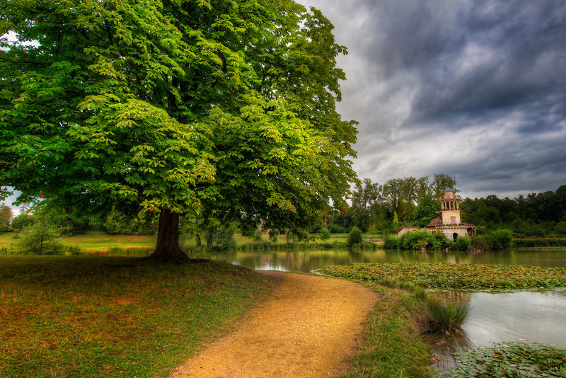 """<h2>Tree and Path and Little Tower in France</h2> <br/>Walking across the country gardens of Versailles can make you feel as lazy and relaxed as royalty.  And that's not a bad thing.  Well, unless you are a photographer, which means you can't ever just stroll along and forget what you are seeing.  It's a blessing and a curse… the need to always be """"on"""" and taking hyper-notice of everything around you.  I'm glad for it though, really.<br/><br/>- Trey Ratcliff<br/><br/><a href=""""http://www.stuckincustoms.com/2012/02/26/tree-and-path-and-little-tower-in-france/"""" rel=""""nofollow"""">Click here to read the rest of this post at the Stuck in Customs blog.</a>"""