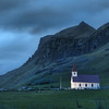 "<h2>A Lonely Night in Iceland</h2> <br/>I was in the southern area of Iceland, only a few kilometers from the big volcano eruption. There was still a bit of ash scattered around, and I was driving down random side-roads. I made a deal with myself that I would randomly take exits off the main highway to see what I could find. This was one of those occasions.<br/><br/>On the way back to the highway, I saw new things. It's hard to have a 360-degree sense of all compositions while driving. Usually my viewing cone is fully stimulated at 180 degrees while moving forward! So, moving back and forth along roads sometimes provides surprises.<br/><br/>I had just spent a few hours around midnight on a black-sand volcanic beach on the shore. I was the only one there, as usual. It's very creepy, in a way, being on a gigantic black beach in the middle of the night without another car or human anywhere in sight. And I know that it is even beyond my sight for a long way because I had not seen anyone on the drive there. I listened to music and took photos all the while, of course. And on the way back, I saw this tiny lit church against some distant mountains, so I popped out for another shot.<br/><br/>- Trey Ratcliff<br/><br/><a href=""http://www.stuckincustoms.com/2010/10/07/a-lonely-night-in-iceland/"" rel=""nofollow"">Click here to read the rest of this post at the Stuck in Customs blog.</a>"