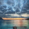 """<h2>The Pier at the End of Times</h2> <br/>Here is a good tip for you when it comes to sunsets.  It also works if you have something in the center worthy of attention, which is commonly the case with sunsets.<br/><br/>When you use a wide-angle lens, like this 14-24, you will automagically get a feeling that everything is pointed to the middle.  That is obvious, but you can """"help the cause"""" and make the effect more pronounced by doing the following.  If the there are repeating elements of roughly the same size (in this case: 1- slats of a dock and 2- blobs of clouds), then those elements will create leading lines to the horizon as they get logarithmically smaller towards the infinity point.  In a sense, the slats only do part of the job, but the clouds do the rest of the job.  Then, this allows you to have leading lines that take people in and out and back around the work.<br/><br/>So, one thing to look for when shooting with the wide angle lens is multiple objects of roughly the same shape.  After that, you can try to set up so they repeat ever smaller towards the horizon.<br/><br/>This particular photo was taken in Ibiza one evening, just after the sun dipped into the Mediterranean.<br/><br/>- Trey Ratcliff<br/><br/><a href=""""http://www.stuckincustoms.com/2011/03/31/peter-lik-your-thoughts/"""" rel=""""nofollow"""">Click here to read the rest of this post at the Stuck in Customs blog.</a>"""